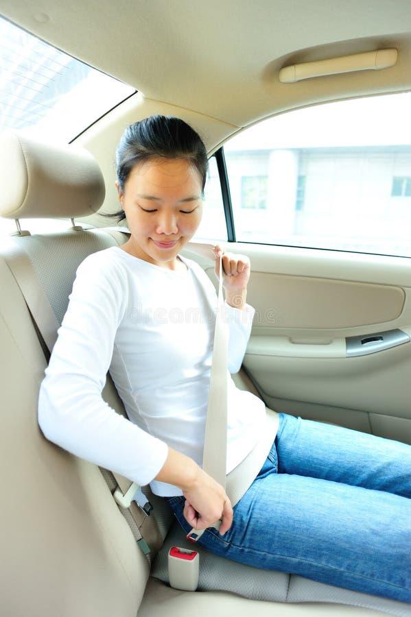 Frauenschnalle herauf den Sicherheitsgurt stockbilder