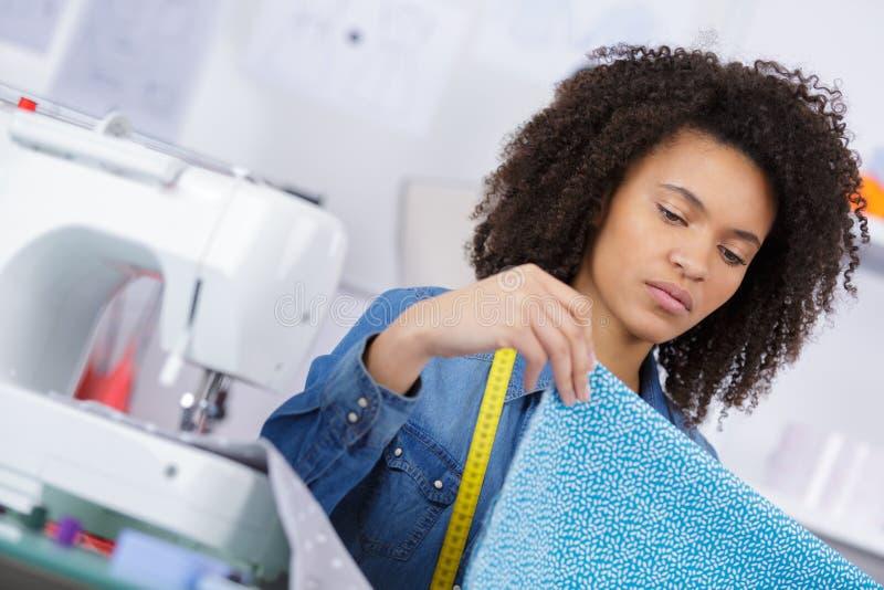 Frauenschneider, der an neuer Kleidung arbeitet lizenzfreie stockfotos