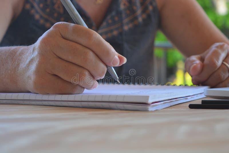 Frauenschreiben auf einem Notizblock, Nahaufnahme des Stiftes in der Hand lizenzfreies stockfoto
