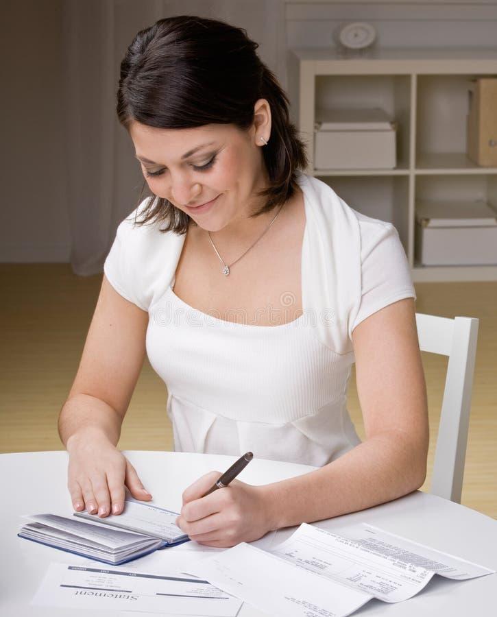 Frauenschreibenschecks vom Scheckheft lizenzfreie stockfotografie