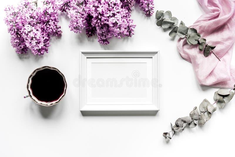 Frauenschreibtisch mit Rahmen-, Kaffee- und Fliederblüte entwerfen weißes Draufsichtmodell des Hintergrundes stockbild