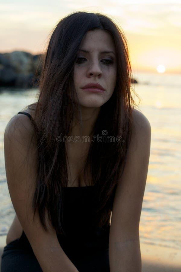 Frauenschreien hoffnungslos bei Sonnenuntergang vor dem Ozean stockfotografie