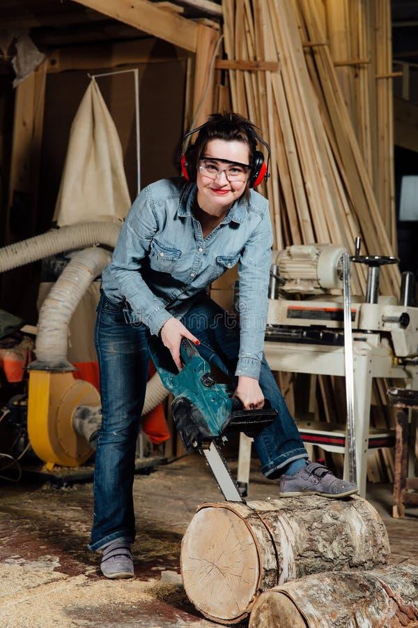 Frauenschreiner in der Werkstatt sägt den Baum mit einer elektrischen Kettensäge Tischler bei Sawing stockfotos