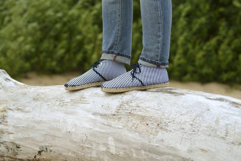 Frauenschuhe und Jeans und Balken lizenzfreie stockbilder