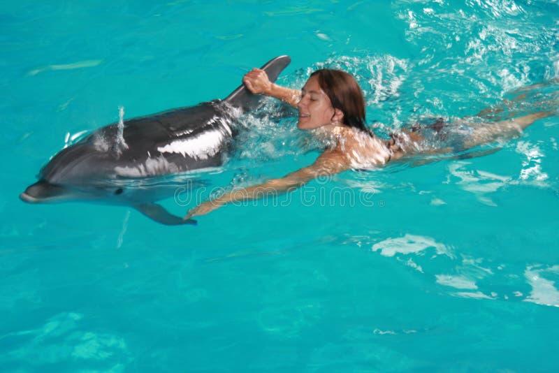Frauenschwimmen mit Delphin lizenzfreies stockfoto