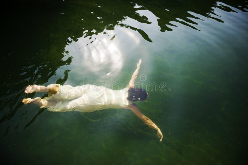 Frauenschwimmen unter Wasser stockfotografie
