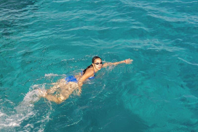Frauenschwimmer-Schwimmenschleichen im blauen Meer Frauenschwimmen im Meer Glückliche junge Frau in einem blauen Badeanzug im Mee stockfoto