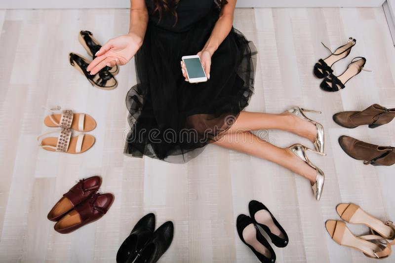 Frauensitzen auf Boden umgab viele Schuhe lizenzfreies stockbild