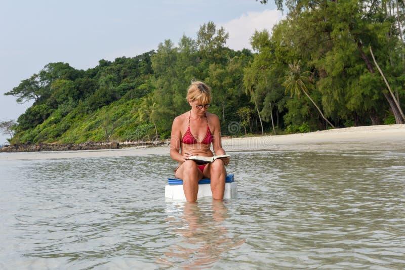 Frauensitzen- und -lesebuch auf Strand stockbilder