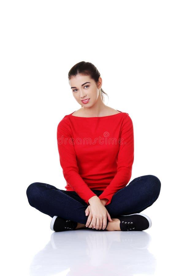 Frauensitzen in voller Länge im Schneidersitz lizenzfreie stockbilder