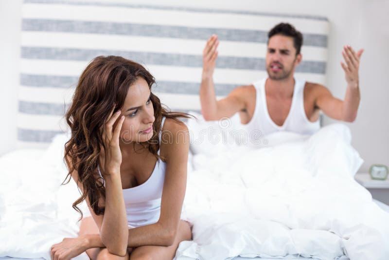 Frauensitzen während Ehemann, der an ihr schreit lizenzfreies stockbild