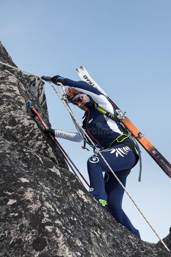 Frauenskibergsteiger, der auf dem Felsen auf einem Seil klettert lizenzfreies stockbild