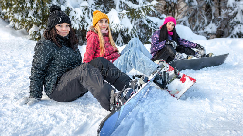 Frauensnowboarder, die auf dem Schnee sitzen lizenzfreie stockbilder