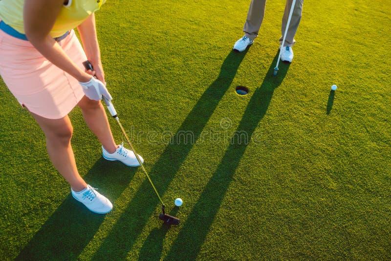 Frauenspieler bereit, den Ball in das Loch am Ende eines Spiels zu schlagen lizenzfreie stockfotos