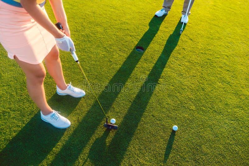 Frauenspieler bereit, den Ball in das Loch am Ende von a zu schlagen lizenzfreie stockfotografie