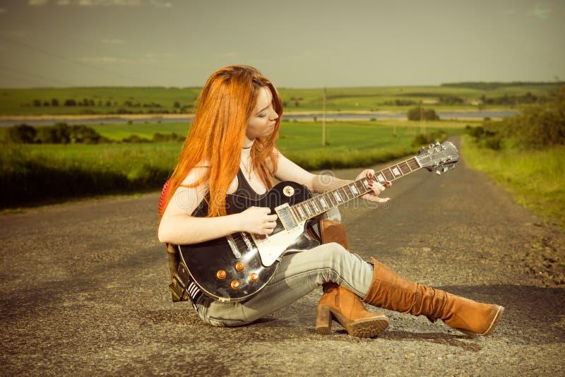 Frauenspielgitarre an der Autobahn lizenzfreies stockfoto
