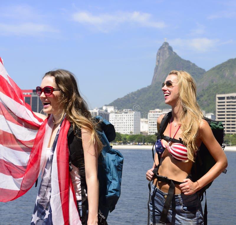 Frauensportfreunde, die USA-Flagge in Rio de Janeiro mit Christus der Erlöser im Hintergrund halten. lizenzfreie stockbilder