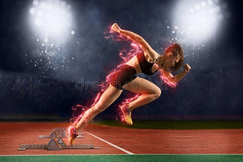 Frauensprinter, der Startblöcke auf der athletischen Bahn lässt stockbilder