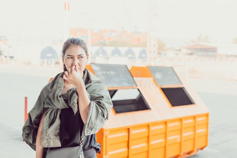 Frauenstand nahe Abfall und sie riechen stinkenden schmutzigen Abfall lizenzfreie stockfotos