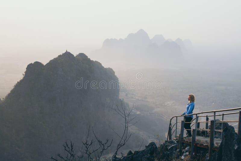 Frauenstellung auf Bergspitze mit der Treppe, die unten während des nebeligen Morgens des Sonnenaufgangs in Hpa-An, Myanmar geht lizenzfreie stockfotos