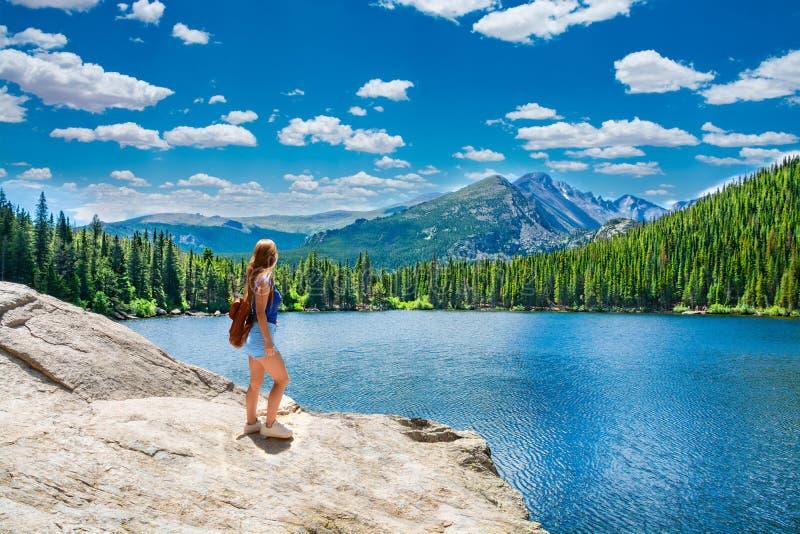 Frauenstellung auf dem Felsen, der schöne Sommerberglandschaft betrachtet, lizenzfreie stockfotos