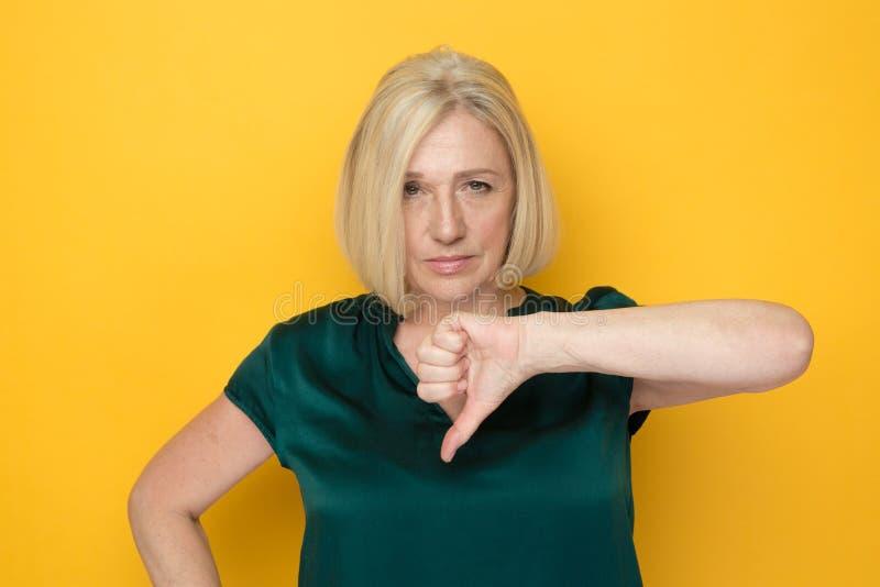 Frauenstellung auf dem gelben Hintergrund und unten dem darstellen Daumen lizenzfreie stockfotos