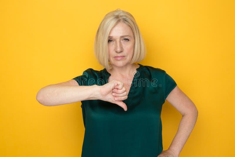 Frauenstellung auf dem gelben Hintergrund und unten dem darstellen Daumen stockfoto