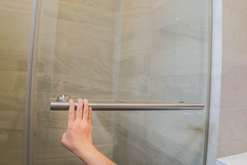 Frauenstoß die Glaskabinentür für das Nehmen einer Dusche im Badezimmer stockfoto