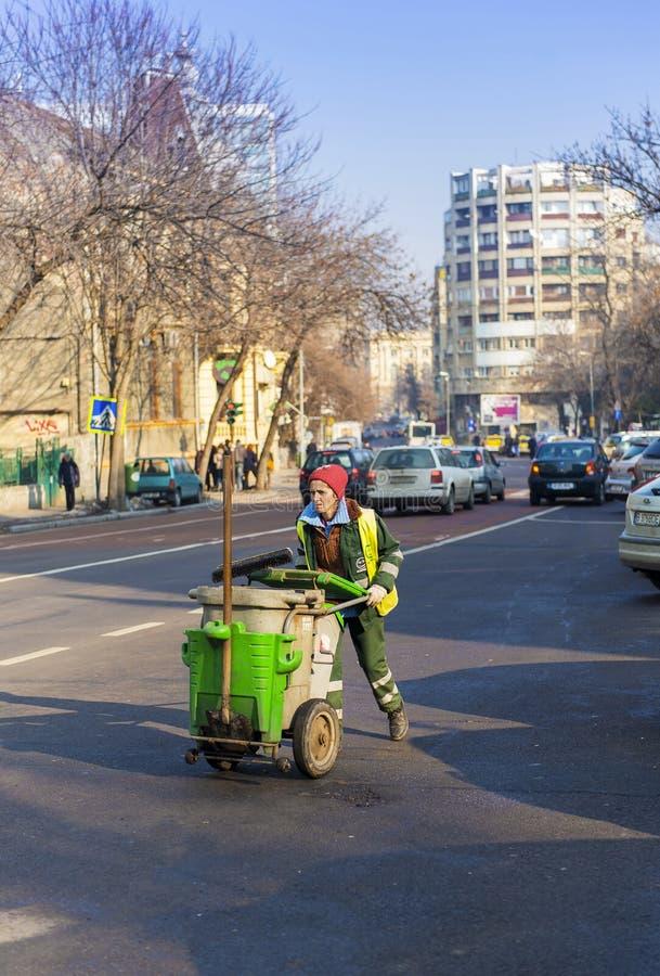 Frauenstraßenarbeitskraft, die eine Reinigungslaufkatze drückt stockbild