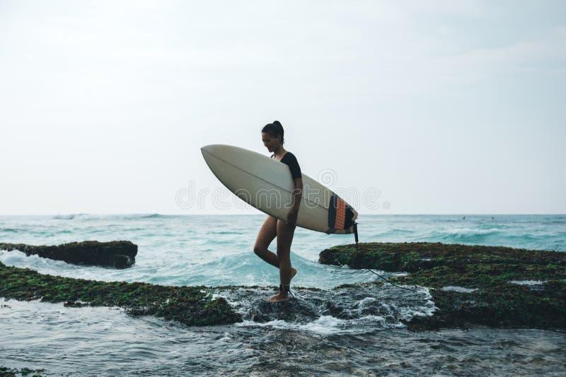 Frauensurfer, der mit Surfbrett geht lizenzfreie stockfotos