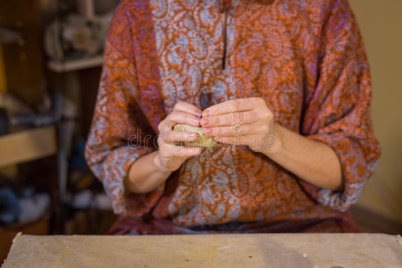 Frauentöpfer, der keramischen Andenkenpenny in der Tonwarenwerkstatt pfeifen lässt stockbild