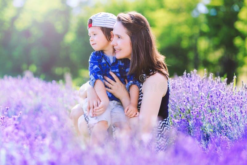 Frauentag Glückliche Frau mit nettem Jungen auf Lavendelhintergrund lizenzfreie stockfotos