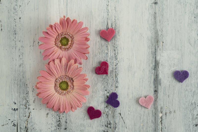 Frauentagesschablone mit Gänseblümchenblumen und -herzen auf Holz lizenzfreie stockbilder