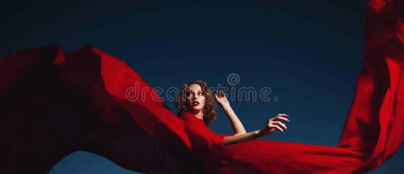 Frauentanzen im Seidenkleid, in k?nstlerisches rotes Schlagkleiderwellenartig bewegendem und flittering Gewebe stockfotografie