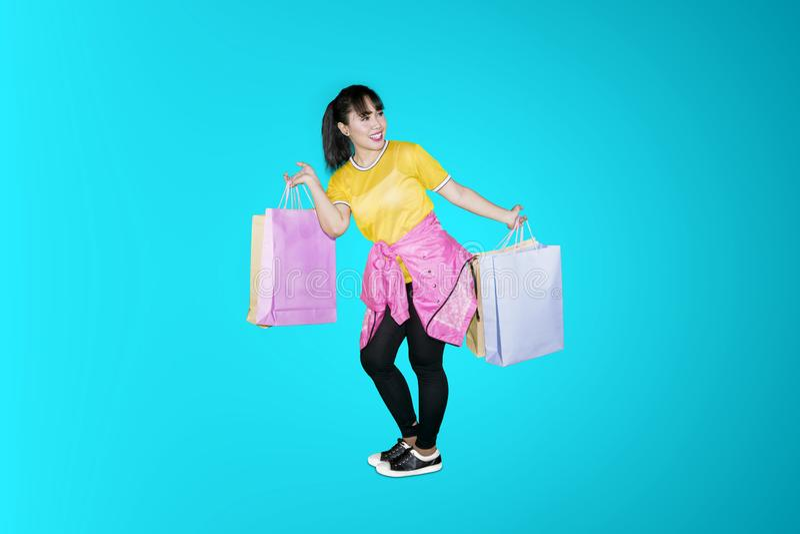 Frauentanzen im Studio mit Einkaufstaschen lizenzfreie stockfotografie