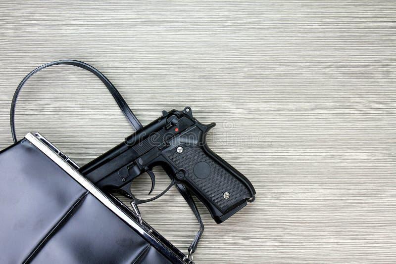 Frauentasche mit dem Gewehr versteckt, Pistole, die von einem Frau ` s Geldbeutel fällt stockbild