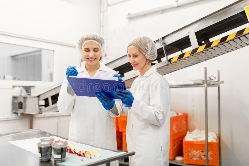 Frauentechnologen, die Eiscreme an der Fabrik schmecken lizenzfreies stockfoto