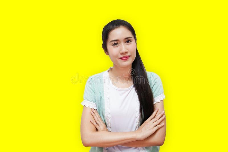 Frauenthailänders junger Dame des Porträts tragende weiße Stellung T-Shirt des glücklichen lokalisiert über gelbem Hintergru stockfoto