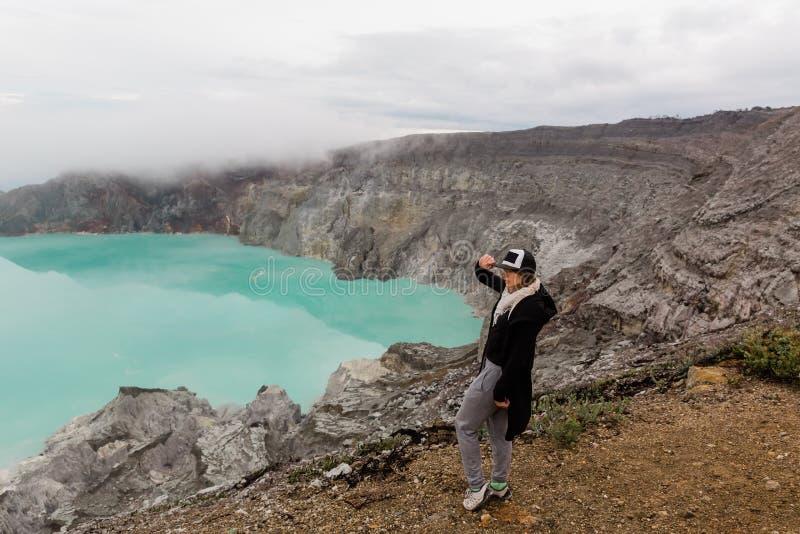 Frauentourist betrachtet den Schwefelsee auf dem Ijen-Vulkan auf der Insel Java in Indonesien Weibliche Reise des Wanderers auf d stockfoto