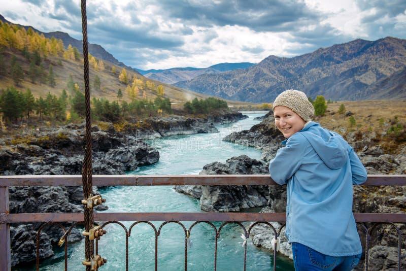 Frauentourist in den Strickmützeständen auf Brücke über dem Fluss Erwachsene Frau des Porträts, lächelnd und betrachten Kamera au stockfoto