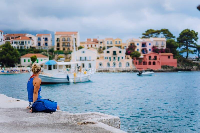 Frauentourist, der auf dem Pier sitzt und zur malerischen Bucht schaut Assos-Dorf mit schönen traditionellen Häusern auf Sommer lizenzfreie stockbilder
