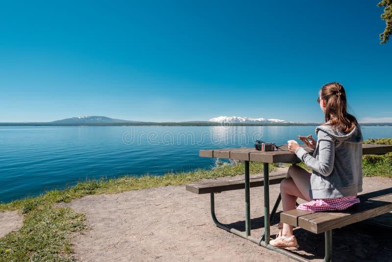 Frauentourist, der durch Yellowstone See frühstückt lizenzfreies stockbild