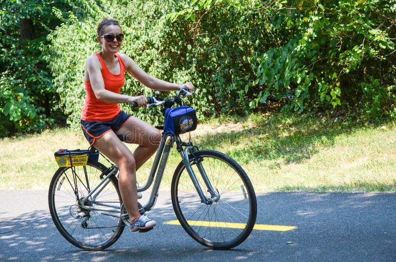 Frauentourist fährt aufwärts auf ein Fahrrad vom Fahrrad- und Rollenfahrrad das Mietkommissionsgeschäft, das herein basiert wird stockbilder