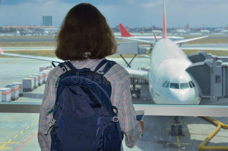 Frauentourist in Flughafenabfertigungsgebäudewarteflug und Betrachten des Flugzeuges stockfotos