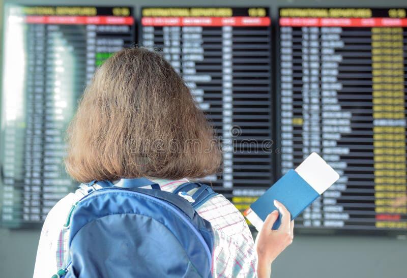 Frauentourist in Flughafenabfertigungsgebäudewarteflug und Betrachten des Zeitplanes mit Pass und Karte lizenzfreie stockfotos