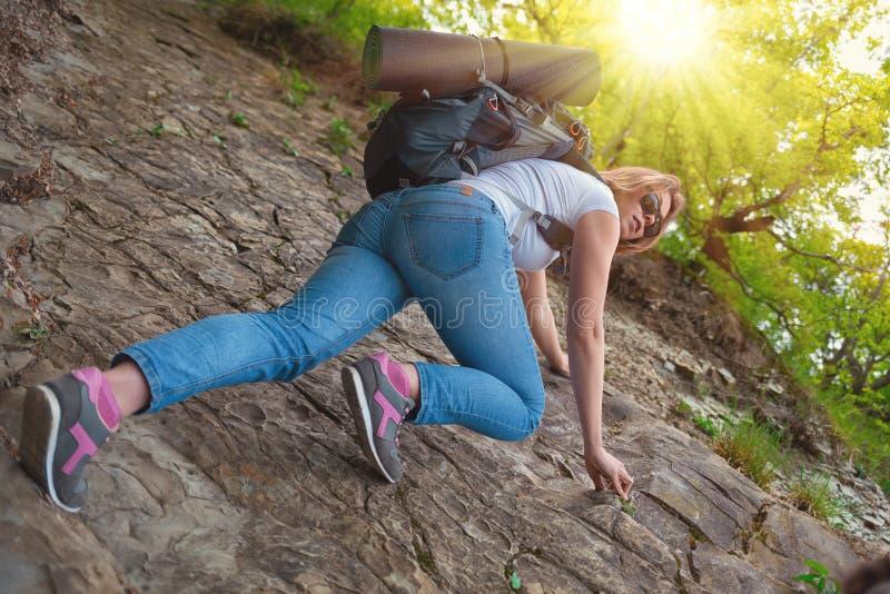 Frauentourist klettert den Felsen Tourismus und Wandern Hintergr?nde: Sonneleuchte Ansicht von unten stockbilder