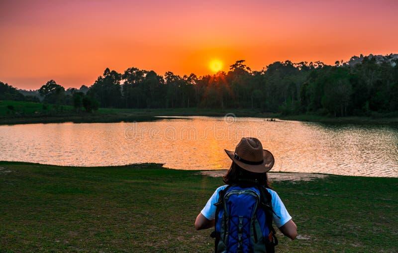 Frauentourist mit Hut und der Rucksack, der mit steht, entspannen sich Stimmung und aufpassenden Sonnenuntergang hinter dem Teich stockbilder