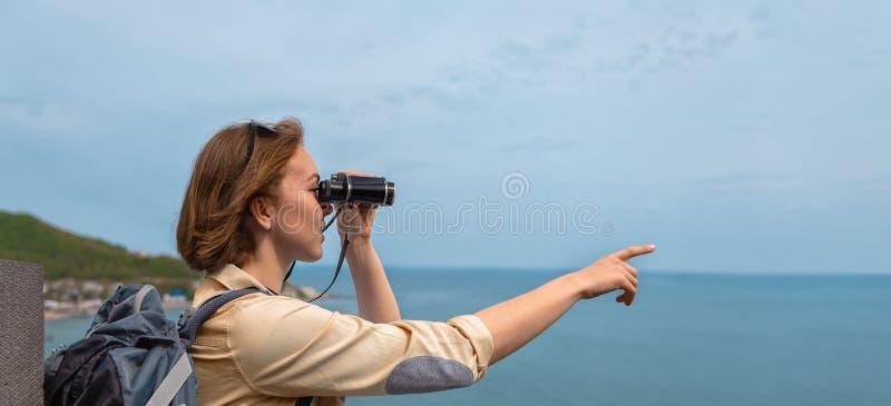 Frauentourist schaut durch Ferngl?ser und Punkte zu etwas mit seiner Hand Blauer Himmel und Meer im Hintergrund Kopieren Sie Plat lizenzfreie stockfotografie