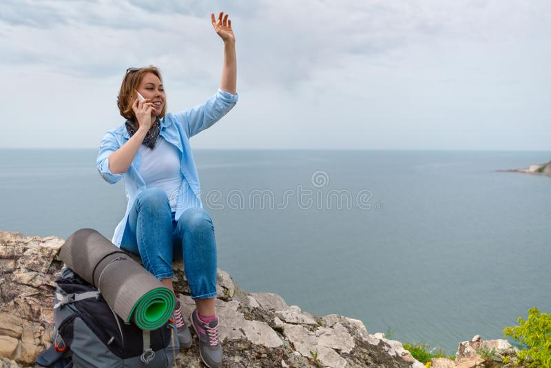 Frauentourist stoppte an einem Halt und entschied sich, seine Familie am Telefon anzurufen Meer und Himmel auf dem Hintergrund stockfotografie