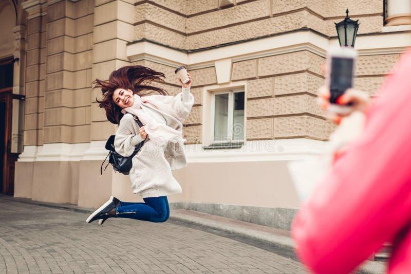 Frauentouristen, die Foto ihres Freunds springt durch Odessa-Opernhaus machen Glückliche Freundreisende, die Spaß haben lizenzfreies stockfoto